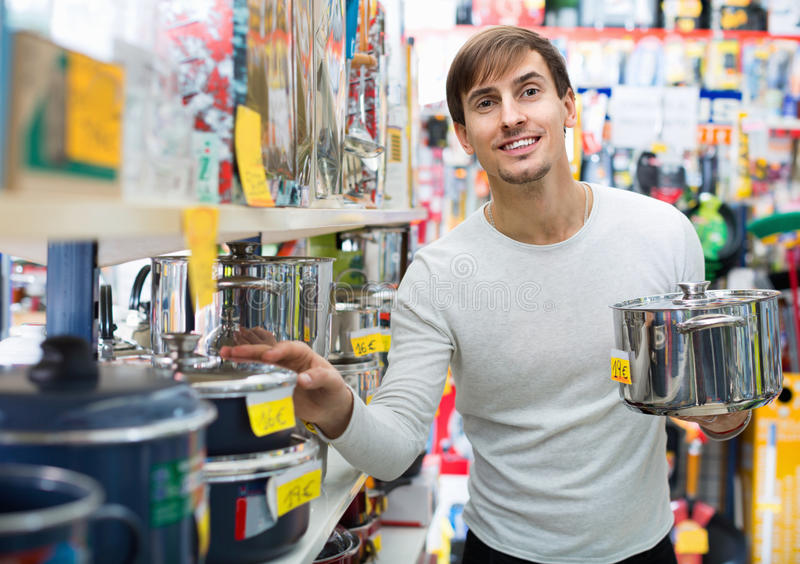 Glücklicher lächelnder junger Mann, der neue metallische Wanne kauft lizenzfreies stockfoto