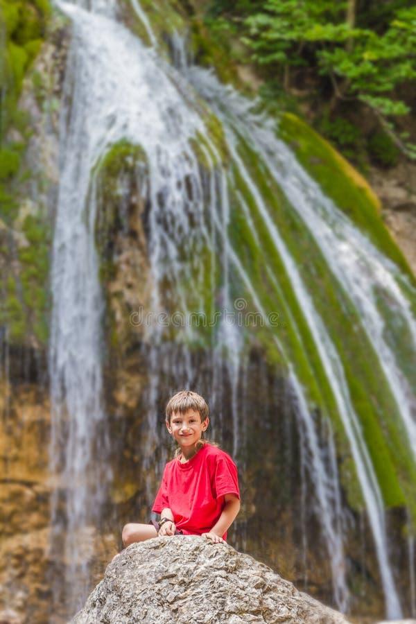 Glücklicher lächelnder Kinderjunge auf Wasserfallhintergrund lizenzfreie stockbilder