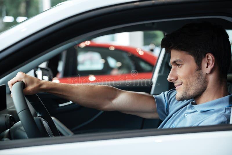 Glücklicher lächelnder männlicher Kunde, der seinen Neuwagen prüft stockfotografie