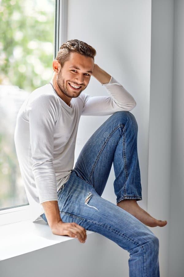 Glücklicher lächelnder Mann, der auf Fensterbrett sich entspannt stockfoto
