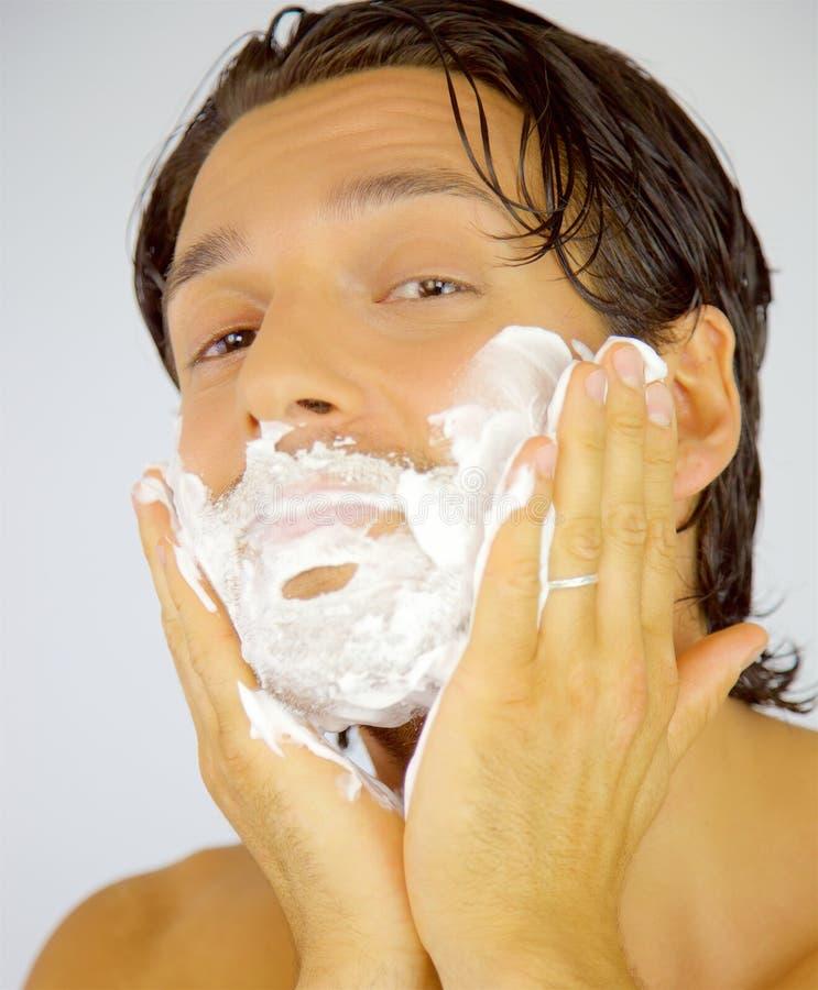 Glücklicher lächelnder Mann, der Creme auf Gesicht aufträgt, bevor schauende Kamera rasiert wird stockbild
