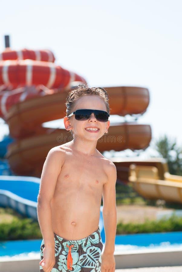 Glücklicher lächelnder netter liitle Junge kurz gesagt und Sonnenbrille im Wasser parkt mit Wasserrutschen im Sommer stockfotos