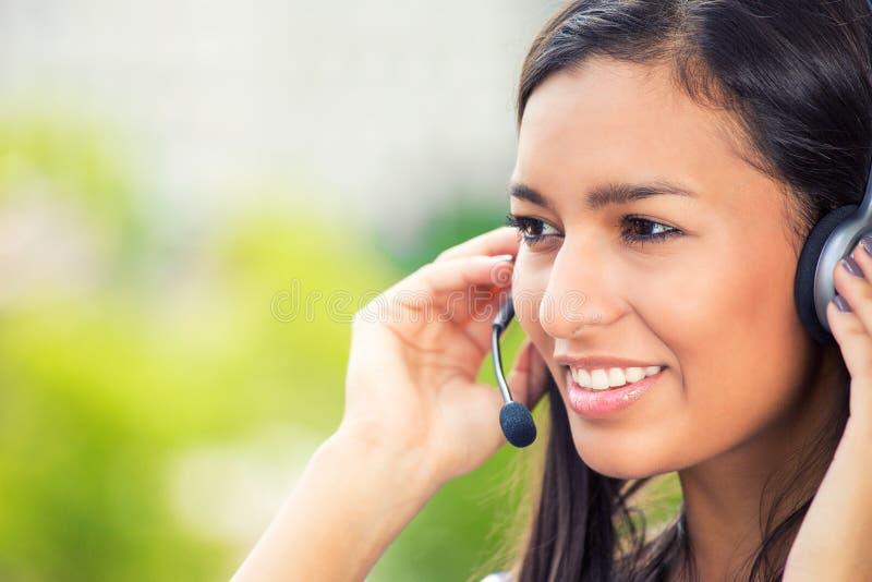 Glücklicher lächelnder netter Stütztelefonbetreiber wuth Kopfhörer stockfoto