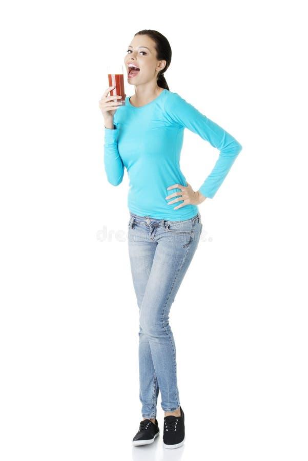 Glücklicher lächelnder trinkender Tomatensaft der Frau lizenzfreie stockfotos