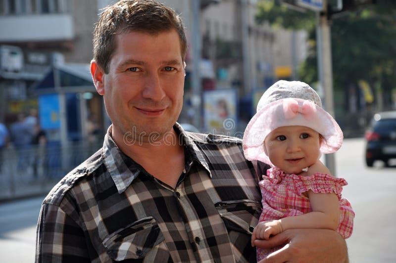 Glücklicher lächelnder Vater mit nettem Baby in einem Hut lizenzfreie stockfotos