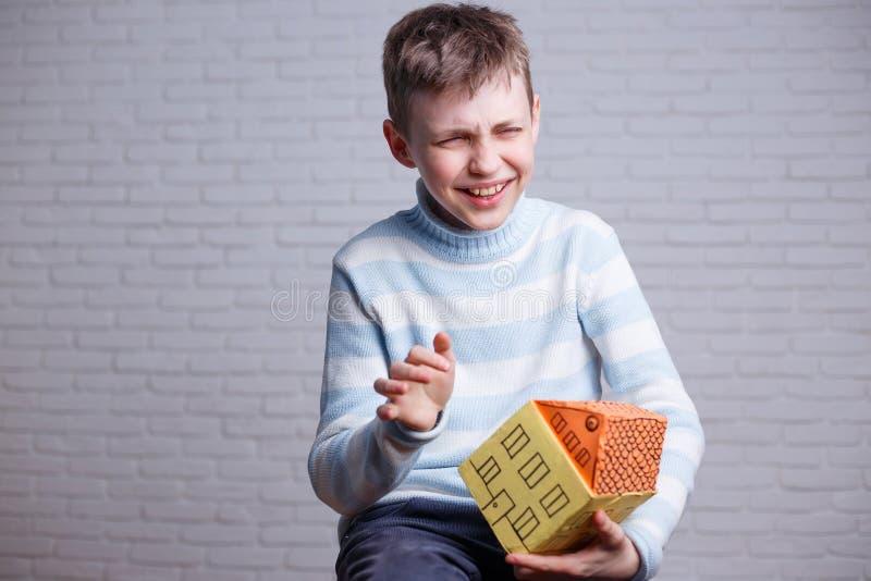Glücklicher lachender Junge mit Pappspielzeughaus in den Händen kindheit lizenzfreie stockfotografie