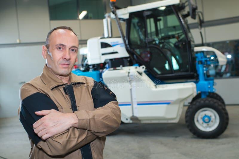 Glücklicher Landwirt nahe bei Traktor stockfoto
