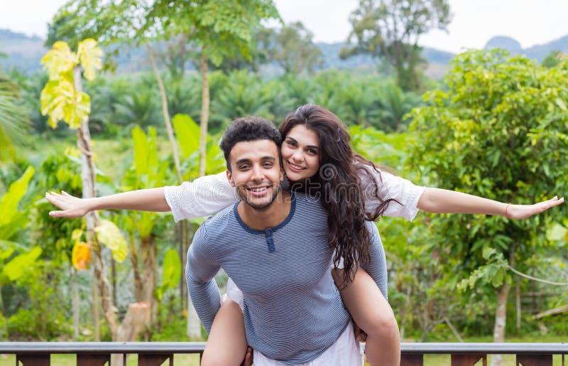 Glücklicher lateinischer Mann Carry Woman On Back, junges Paar über grünem tropischem Regen Forest Landscape lizenzfreie stockbilder