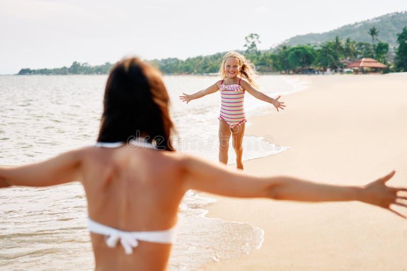 Glücklicher Lauf des kleinen Mädchens zu ihrer Mutter für Umarmungen auf tropischem Strand stockfotos