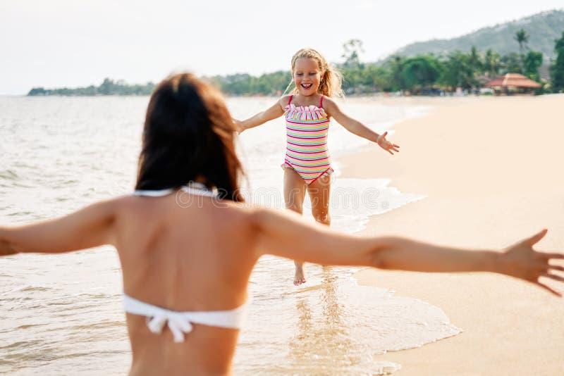 Glücklicher Lauf des kleinen Mädchens zu ihrer Mutter für Umarmungen auf tropischem Strand stockfotografie