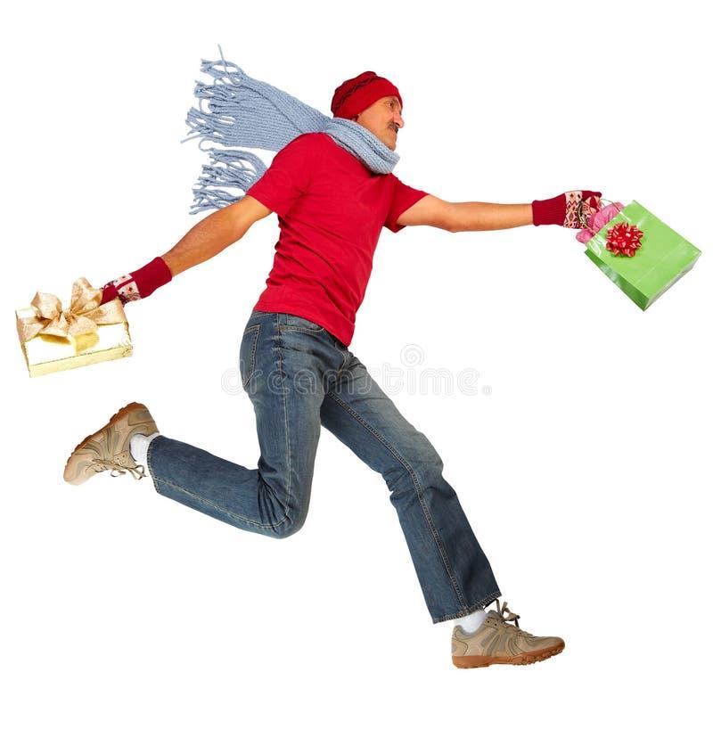 Glücklicher laufender Mann mit Weihnachtsgeschenken lizenzfreie stockfotografie
