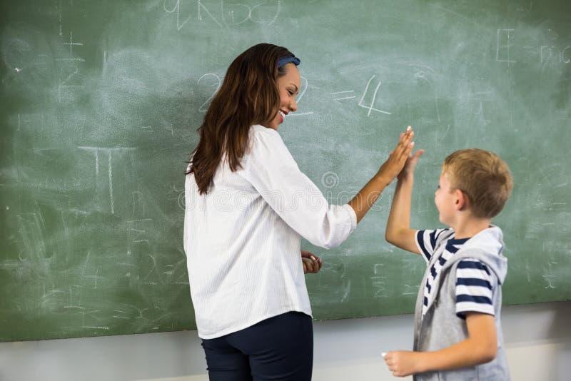 Glücklicher Lehrer und Schuljunge, der Hoch fünf im Klassenzimmer gibt lizenzfreies stockbild