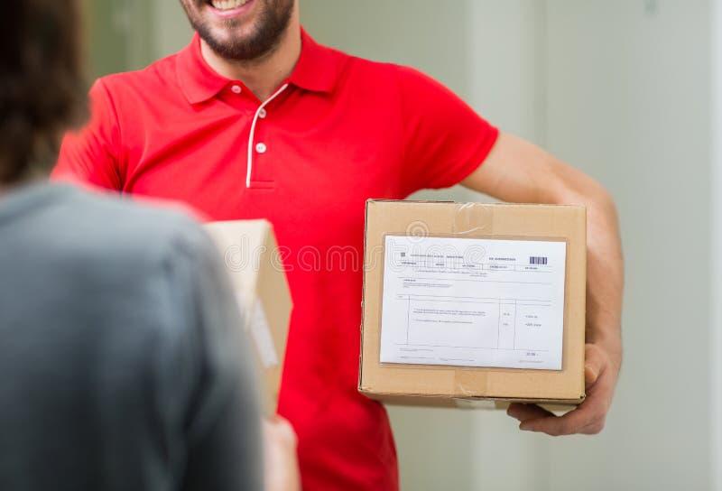 Glücklicher Lieferer mit Paketkasten und -kunden lizenzfreie stockfotografie