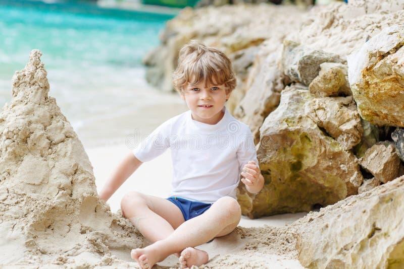 Glücklicher lustiger kleiner Vorschulkinderjunge, der Spaß mit dem Errichten eines Sandburgs auf Ozeanstrand hat Kind, das auf Fa stockfotos