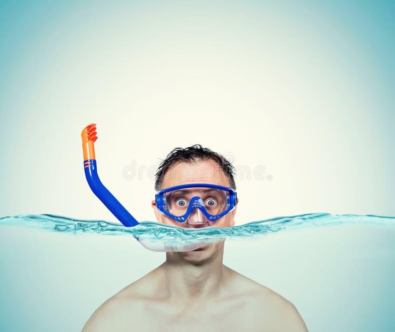 Glücklicher lustiger Mann in einer schwimmenden Maske mit Schnorchel ist im Wasser Seefeiertagskonzept lizenzfreies stockbild