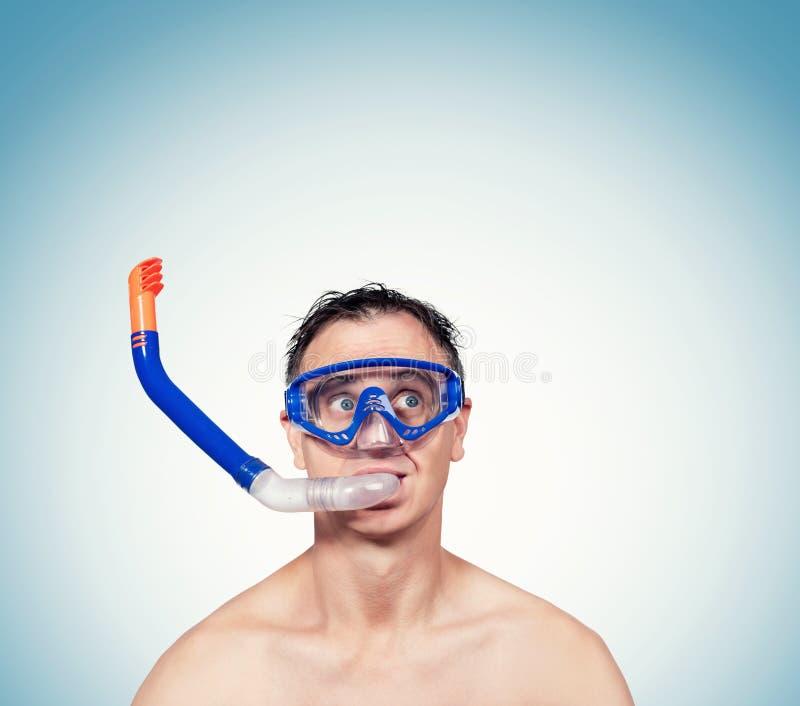 Glücklicher lustiger Mann in einer schwimmenden Maske, mit Schnorchel in seinem Mund auf blauem Hintergrund stockbilder