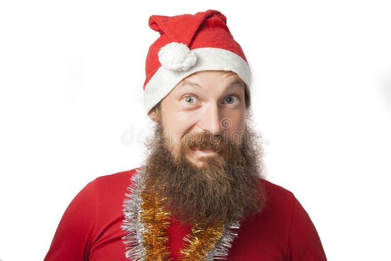 Glücklicher lustiger Weihnachtsmann mit wirklichem Bart und roter Hut und Hemd, die verrücktes Gesicht und das Lächeln, das Schau stockfotografie