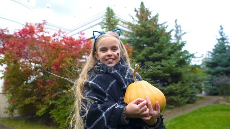 Glücklicher Mädchenholdingkürbis und Aufstellung für Kamera im Halloween-Katzenkostüm lizenzfreie stockbilder