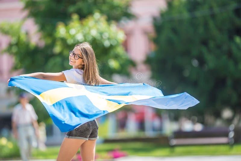 Glücklicher Mädchentourist, der in die Straße mit Schweden-Flagge geht stockfotos