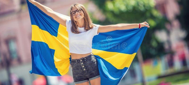 Glücklicher Mädchentourist, der in die Straße mit Schweden-Flagge geht lizenzfreies stockbild