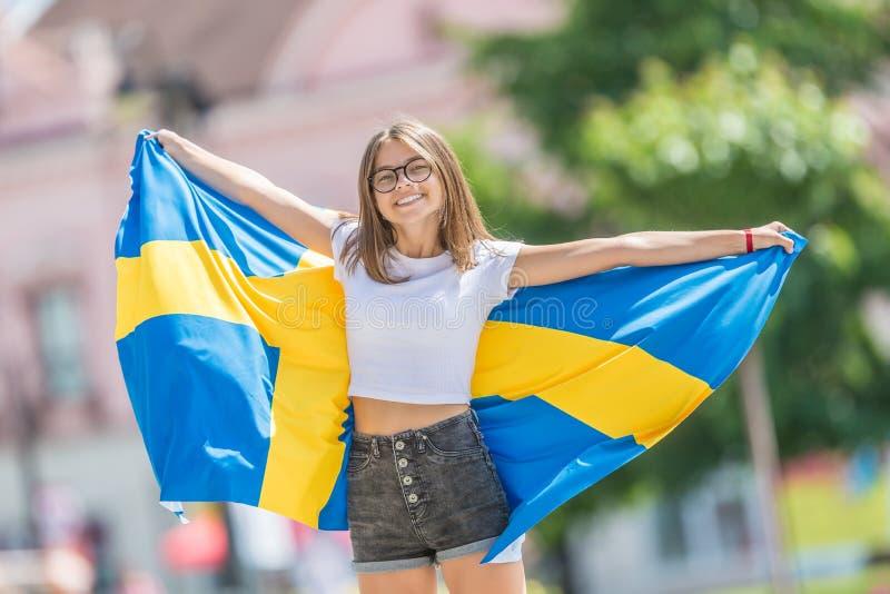 Glücklicher Mädchentourist, der in die Straße mit Schweden-Flagge geht lizenzfreie stockfotografie