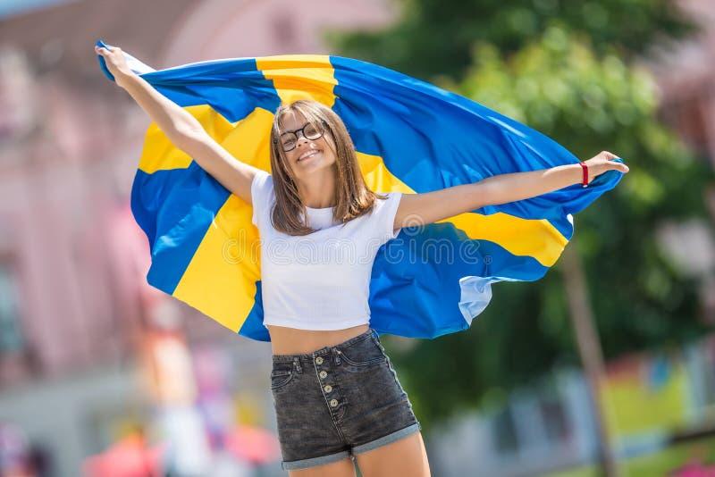 Glücklicher Mädchentourist, der in die Straße mit Schweden-Flagge geht lizenzfreie stockbilder
