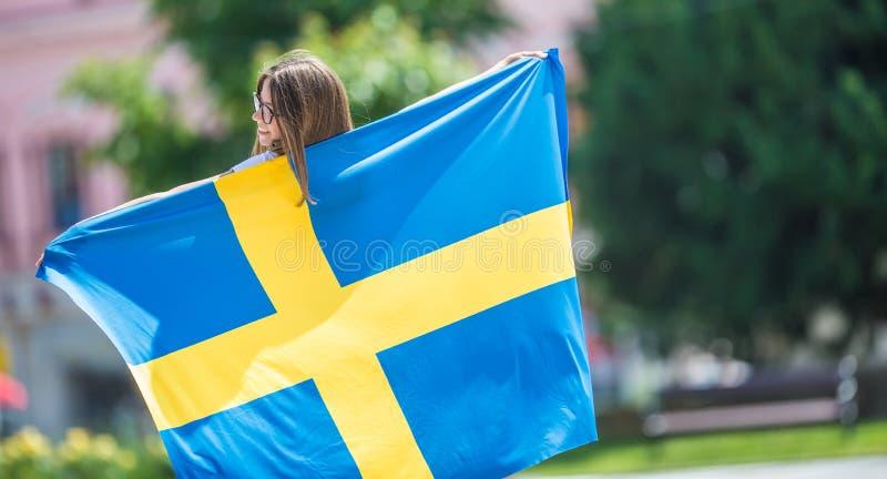 Glücklicher Mädchentourist, der in die Straße mit Schweden-Flagge geht stockbild