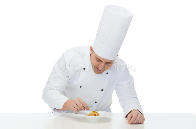 Glücklicher männlicher Chefkoch, der Teller verziert lizenzfreies stockbild