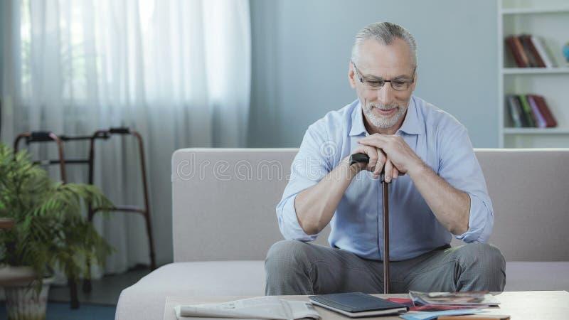 Glücklicher männlicher Pensionär, der auf Couch in Rehabilitationszentrum, Wiederaufnahmezeitraum sitzt stockfotografie
