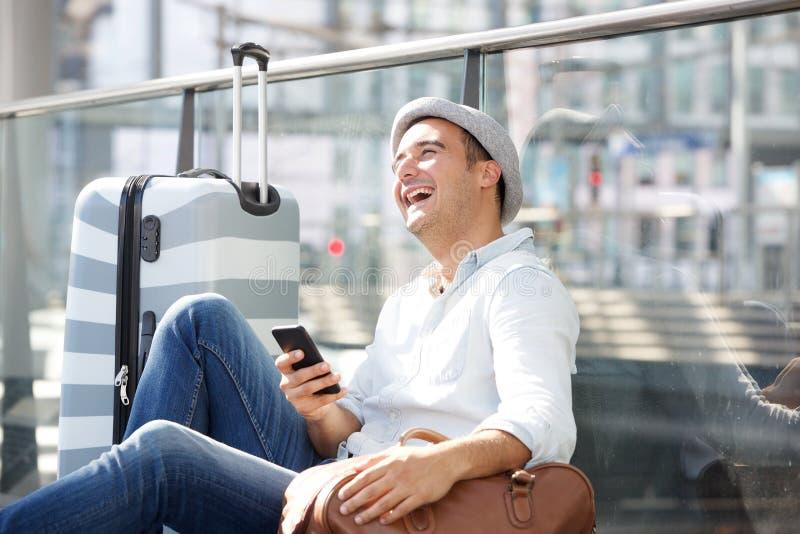 Glücklicher männlicher Reisender, der auf Boden der Station mit Handy und Taschen sitzt stockfotografie