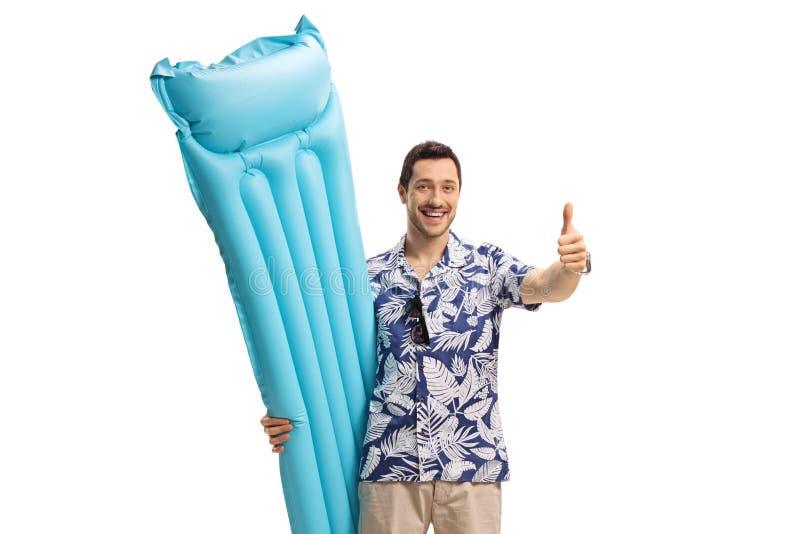 Glücklicher männlicher Tourist mit einer Luftmatraze, die seinen Daumen hochhält lizenzfreie stockfotografie