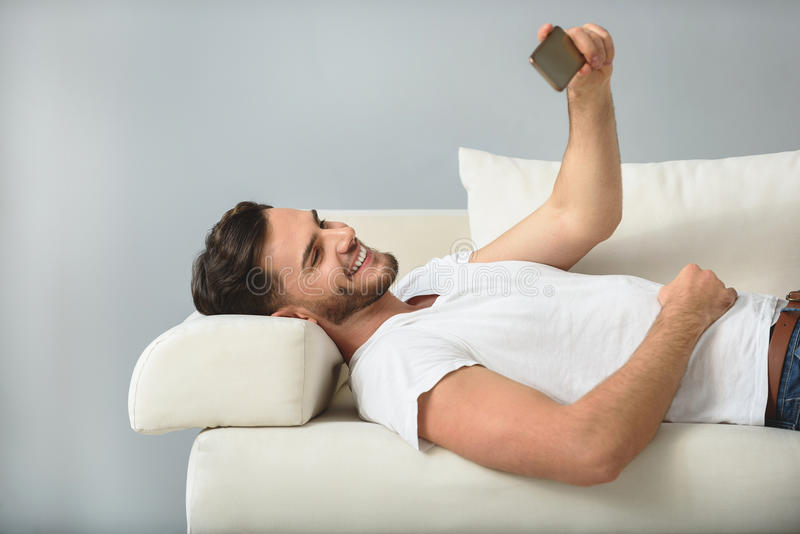Glücklicher Mann auf einem Sofa mit Telefon stockbilder