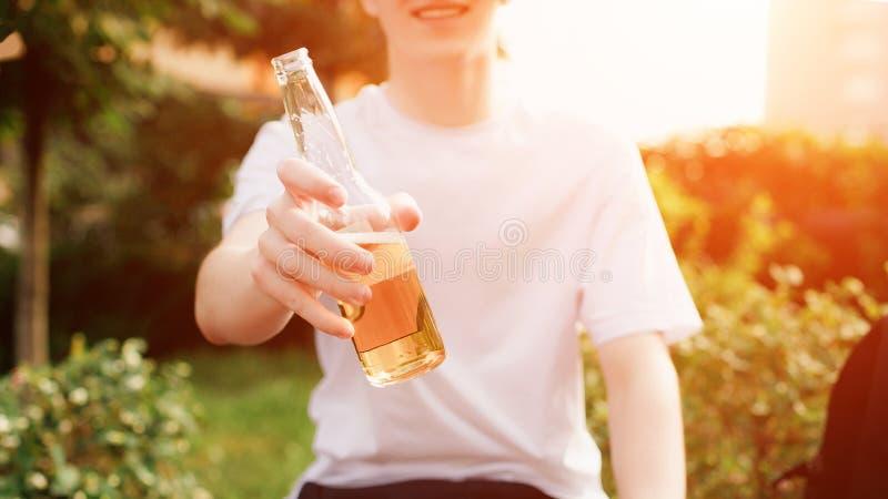 Glücklicher Mann bietet eine Flasche Bier auf Kamera an tageslicht lizenzfreie stockfotos