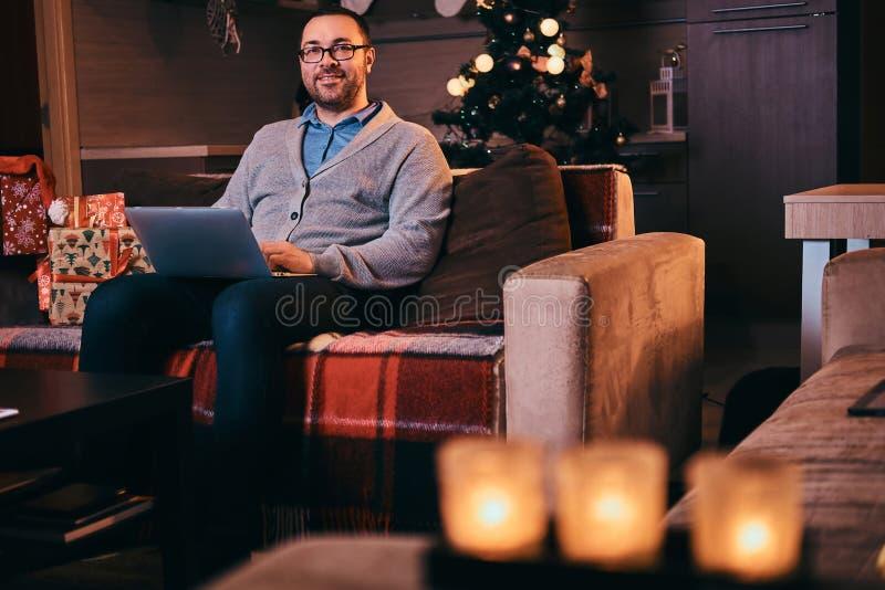 Glücklicher Mann in den Gläsern gekleidet im warmen Strickjackengrifflaptop und im Betrachten der Kamera beim Sitzen auf Sofa zur stockfotos