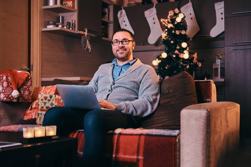 Glücklicher Mann in den Gläsern gekleidet im warmen Strickjackengrifflaptop und im Betrachten der Kamera beim Sitzen auf Sofa zur lizenzfreie stockfotos
