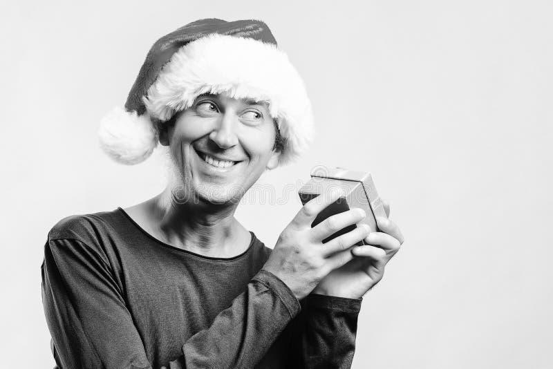 Glücklicher Mann in den Sankt-Helferhüten mit Geschenkbox Winterurlaub- und Weihnachtskonzept Auspacken des Geschenks Isolat auf  lizenzfreies stockfoto