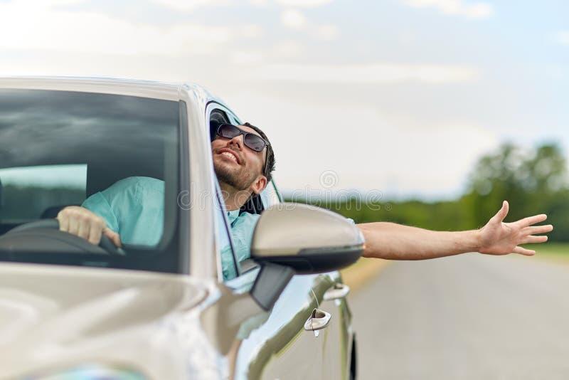 Glücklicher Mann in den Schatten, die Auto fahren und Hand wellenartig bewegen lizenzfreies stockbild