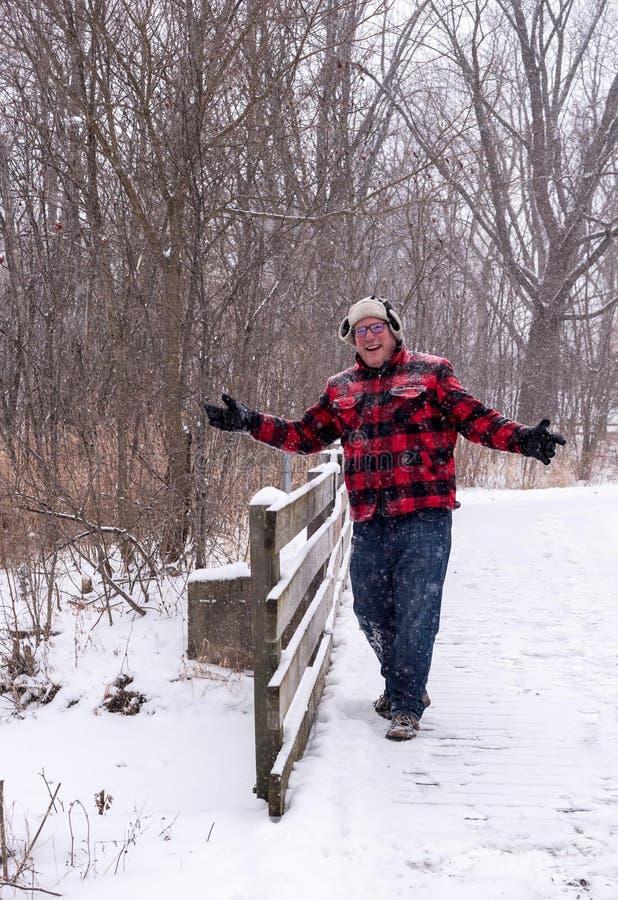 Glücklicher Mann, der über eine Holzbrücke im Schnee geht lizenzfreies stockbild