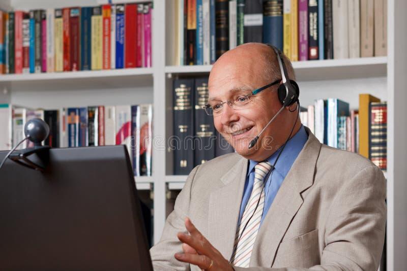 Glücklicher Mann, der über Internet telefoniert lizenzfreie stockfotografie