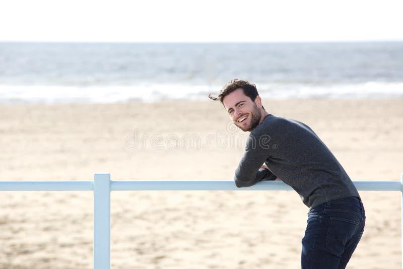 Glücklicher Mann, der allein am Strand steht stockfoto