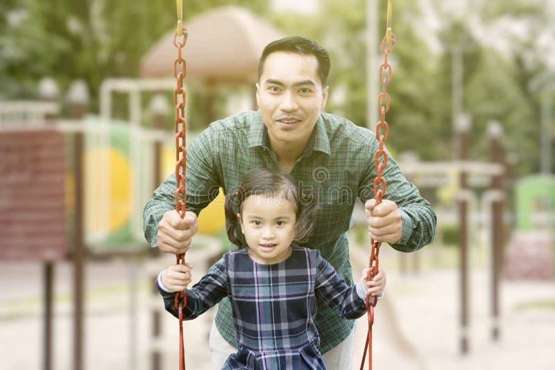 Glücklicher Mann, der auf einem Schwingen mit seiner Tochter spielt stockfoto