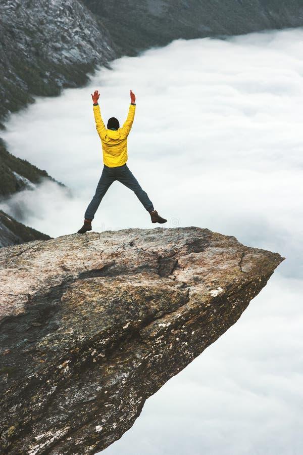 Glücklicher Mann, der auf felsigen Klippenrand Trolltunga springt stockfoto