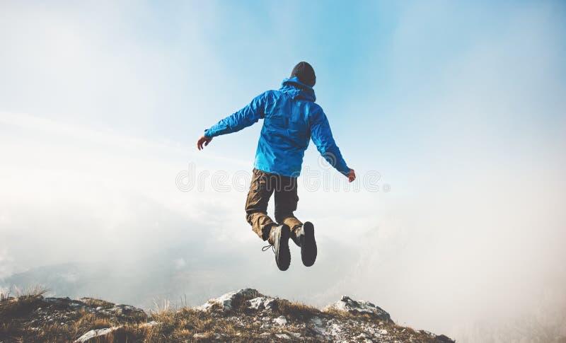 Glücklicher Mann, der auf Gebirgsklippe zum Wolkenhimmel springt stockfotografie