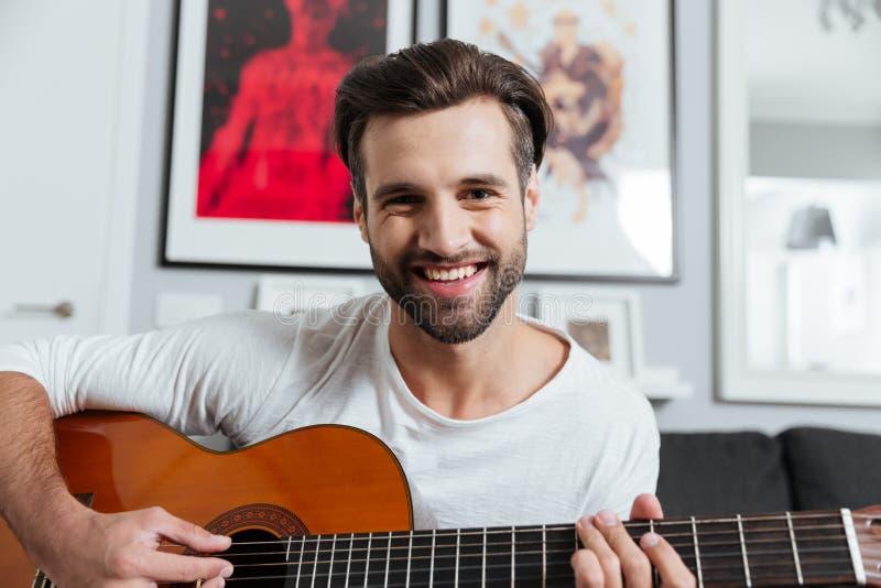 Glücklicher Mann, der auf Gitarre spielt Betrachten der Kamera lizenzfreies stockfoto