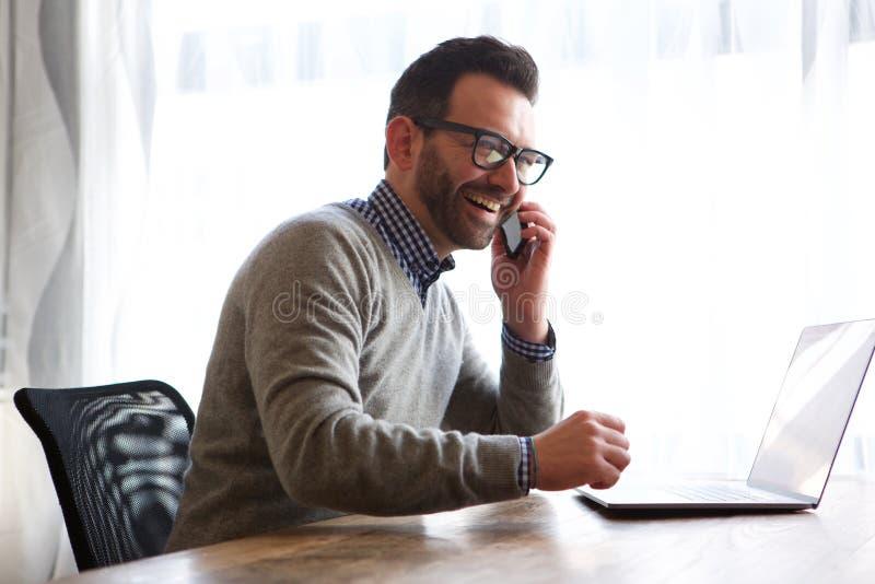 Glücklicher Mann, der auf Mobiltelefon vor Laptop-Computer spricht stockbilder