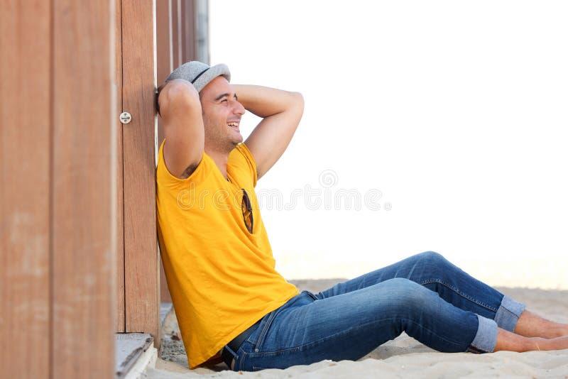 Glücklicher Mann, der auf Sand am Strand mit den Händen hinter Kopf sitzt stockfoto