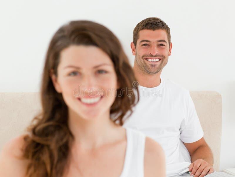 Glücklicher Mann, der auf seinem Bett mit seiner Freundin liegt stockfoto