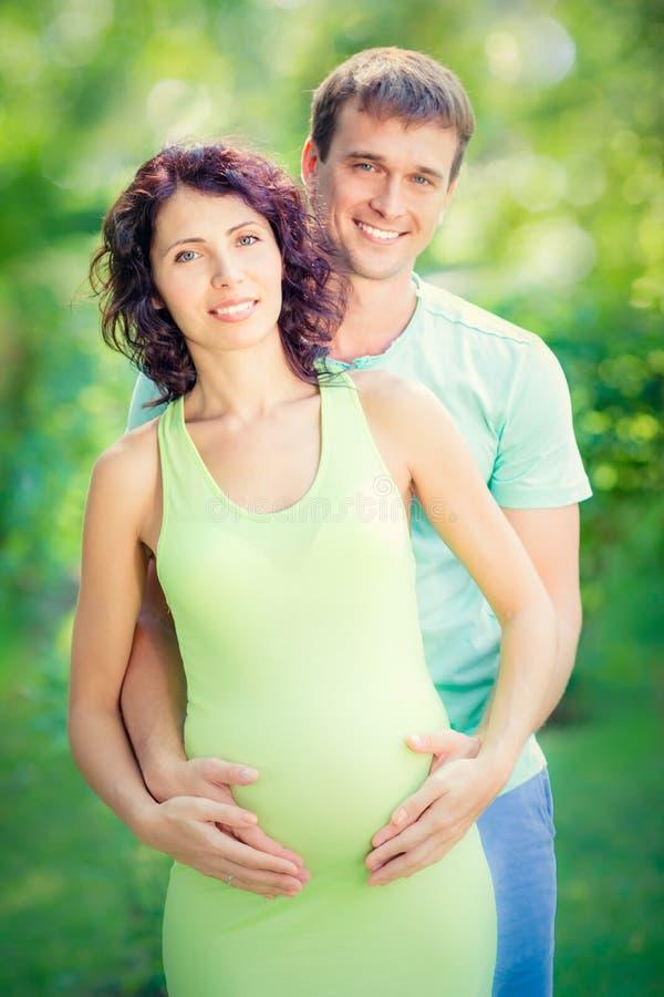 Glücklicher Mann, der Bauch der schwangeren Frau umarmt lizenzfreie stockfotos