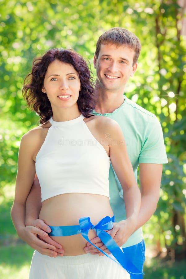 Glücklicher Mann, der Bauch der schwangeren Frau umarmt lizenzfreies stockfoto