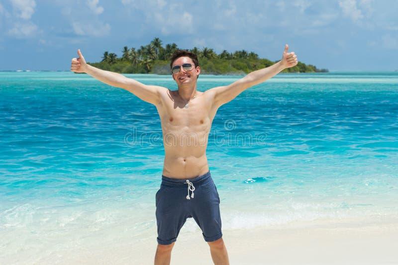 Glücklicher Mann, der Daumen herauf Zeichen am Strand gibt lizenzfreies stockfoto